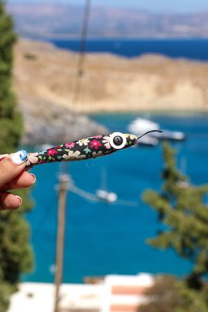 Soft toy colorful fish with a big eye, a button in a female hand with a manicure on the background of a bright Greek summer Rhodes beach