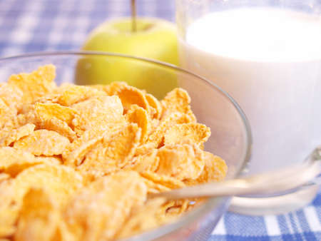 Cornflakes and milk on the table out of the blue tablecloth. Light breakfast.