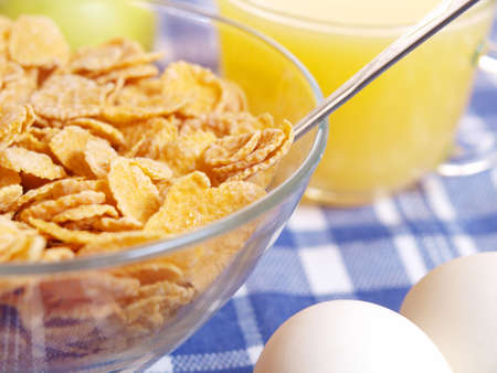 Corn flakes and juice with the eggs on the table.
