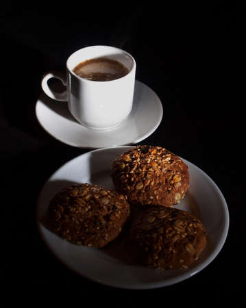A cup of coffee and oatmeal cookies on a black background
