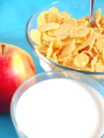 Apple, milk, and corn flakes close up