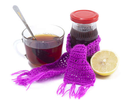 A cup of tea with jam and lemon on a white background