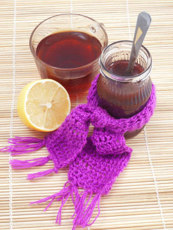 A cup of tea with jam and lemon on the mat photo