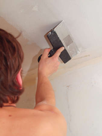 Plasterer is preparing for painting the ceiling. Stock Photo