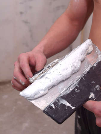 Plasterer is preparing material for the job.