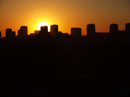 Silhouette of night city on a background of sun