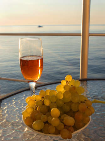 Glass of red wine on the background of the setting of sea and sky