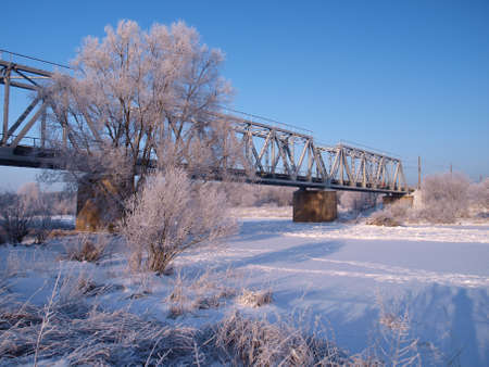 Railway bridge over the river on the background of a winter landscape Stock Photo