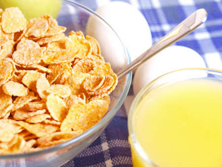 Cornflakes and milk on the table out of the blue tablecloth  Light breakfast          photo