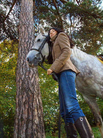 The girl with the horse in a pine forest Stock Photo - 15531000