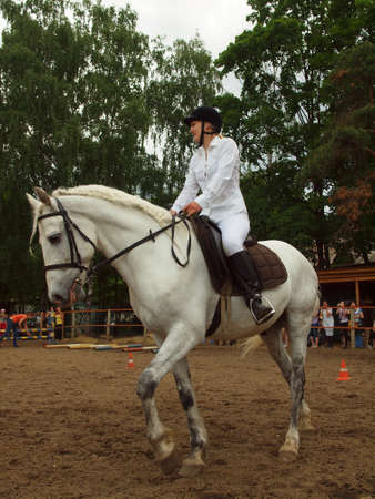 A girl riding a gray horse on the track competitions