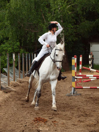 A girl riding a gray horse on the track competitions Stock Photo