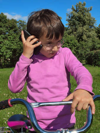 Boy talking on the phone outdoors     photo