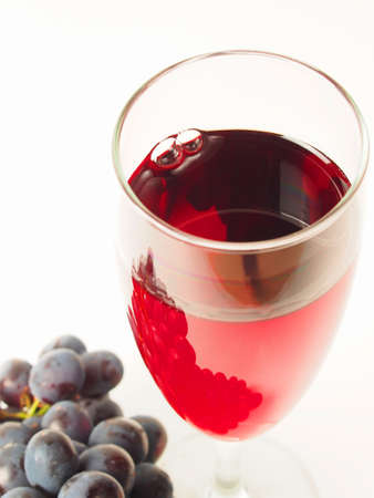 Glass of red wine and dark grapes on a white background
