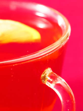 A cup of tea and a lemon on a red background