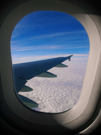 The clouds and the wing of the airplane window