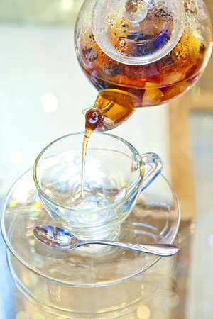 Pouring tea into glass teacup photo