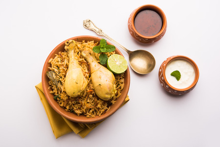 Indian Chicken Biryani served in a terracotta bowl with yogurt over white background. selective focus Banco de Imagens