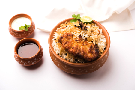 Authentic Fish Biryani served in a white plate over white background, selective focus