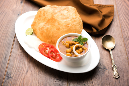 Chole Bhature or Chick pea curry and Fried  Puri served in terracotta crockery over white background. selective focus
