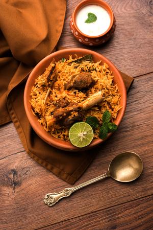 Gosht or Lamb Biryani prepared in Basmati Rice served with Yogurt dip in terracotta bowl. Selective focus Stock Photo