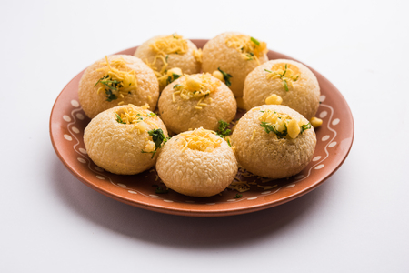 Stuffed Sev Puri is a popular Indian roadside chat item, served in a white plate. Top view, selective focus Stock Photo