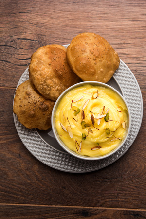 Shrikhand with fried Puri / Poori served in a bowl and plate over moody background. Selective focus