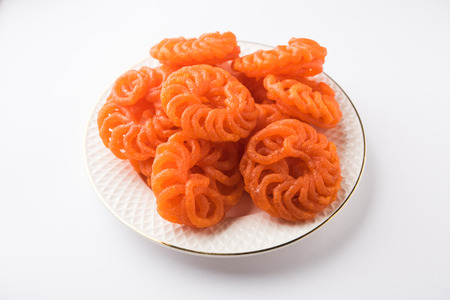 Indian sweet Imarti or Jalebi served in white ceramic plate over white background Stock Photo