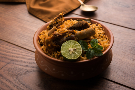Gosht or Lamb Biryani prepared in Basmati Rice served with Yogurt dip in terracotta bowl. Selective focus Stock Photo