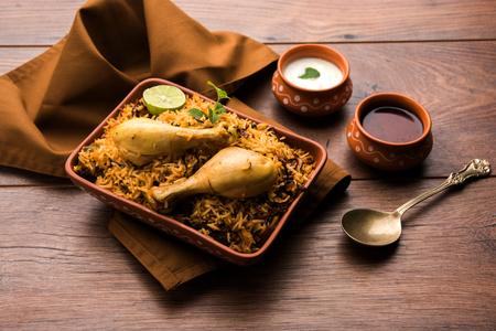 Indian Chicken Biryani served in a terracotta bowl with yogurt over white background. selective focus Standard-Bild