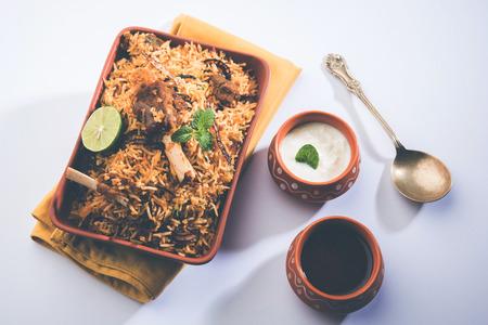 Gosht or Lamb Biryani prepared in Basmati Rice served with Yogurt dip in terracotta bowl. Selective focus Imagens