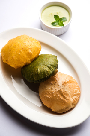 fried Plain Puri , spinach and masala poori served with green chutney, selective focus