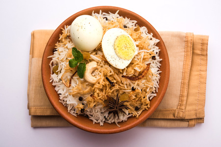 Egg Biryani - Basmati rice cooked with masala roasted eggs and spices and served with yogurt, selective focus Stock Photo