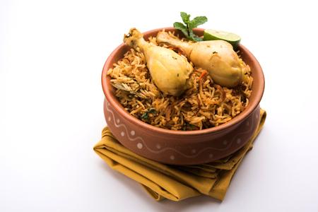 Indyjski kurczak Biryani serwowane w misce z terakoty z jogurtem na białym tle. selektywna ostrość