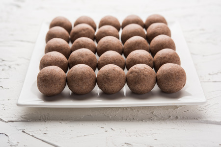 Nachni laddu or Ragi laddoo or balls made using  finger millet, sugar and ghee. It's a healthy food from India. Served in a bowl or plate over moody background. Selective focus