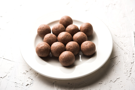 Nachni laddu or Ragi laddoo or balls made using  finger millet, sugar and ghee. Its a healthy food from India. Served in a bowl or plate over moody background. Selective focus