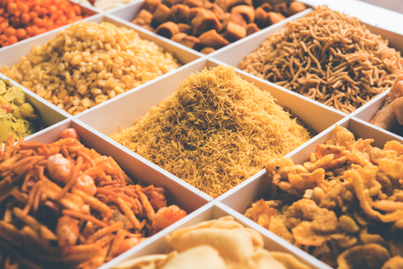 Indian Tea-time snacks like sev, chivda, farsan, mixture, boondi, bakarwadi etc served in white wooden box with cells. selective focus Stock Photo