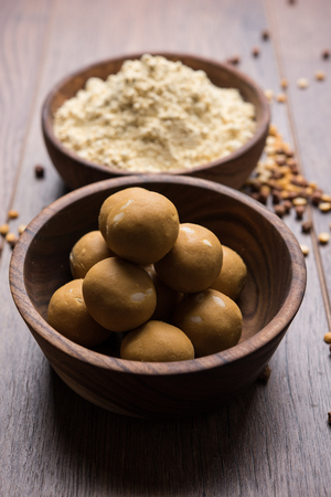 Chick pea flour or Besan powder in a ceramic or wooden bowl along with sweet Laddu or laddoo