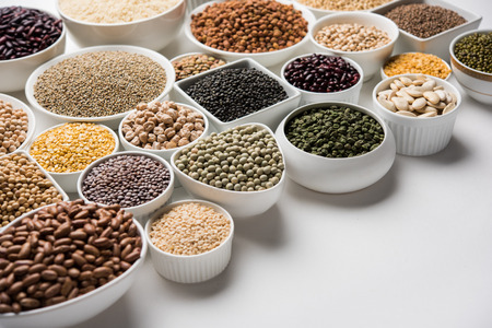 Uncooked pulses,grains and seeds in White bowls over white background. selective focus Stock Photo