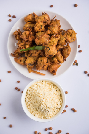 Chick pea flour or Besan powder in a ceramic or wooden bowl along with fried onion pakora or kanda bajji 写真素材