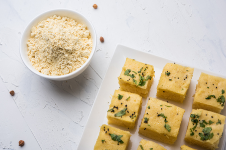 Chick pea flour or Besan powder in a ceramic or wooden bowl along with Gujrati Dhokla snack