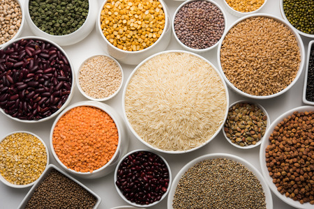 Uncooked pulses,grains and seeds in White bowls over white background. selective focus Stockfoto
