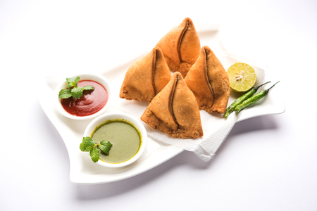 Samosa snack served with tomato ketchup and mint chutney