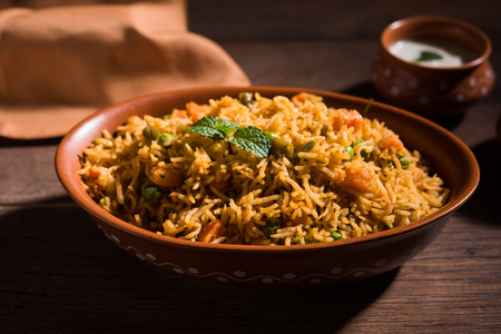 Indian Vegetable Pulav or Biryani made using Basmati Rice, served in terracotta bowl. selective focus Imagens