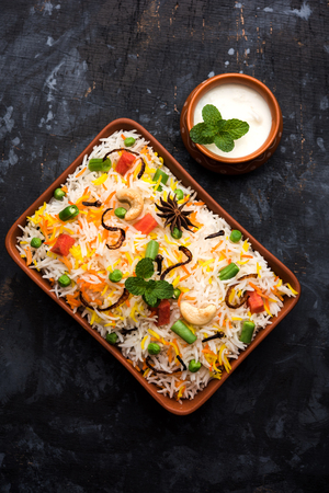 Indian Vegetable Pulav or Biryani made using Basmati Rice, served in a ceramic bowl. selective focus Imagens