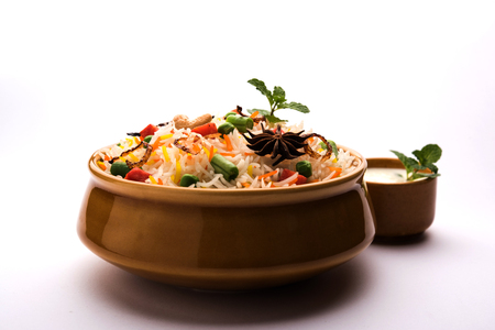 Indian Vegetable Pulav or Biryani made using Basmati Rice, served in a ceramic bowl. selective focus Фото со стока