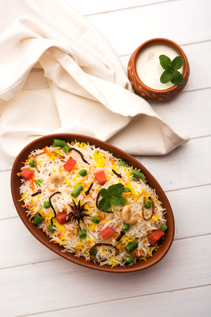 Indian Vegetable Pulav or Biryani made using Basmati Rice, served in a ceramic bowl. selective focus Stock Photo