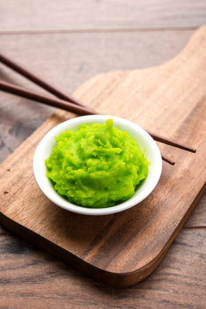 Green wasabi sauce or paste in bowl, with chopsticks or spoon over plain colourful background. selective focus 스톡 콘텐츠