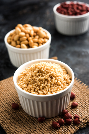 Crushed peanuts or mungfali powder with whole and roasted groundnut. Served in a bowl over moody background. Selective focus