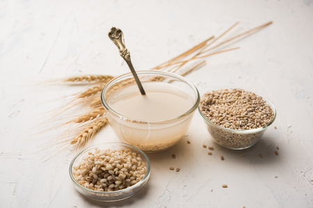 Barley water in glass bowl with spoon and raw and cooked pearl barley wheat/seeds. selective focus